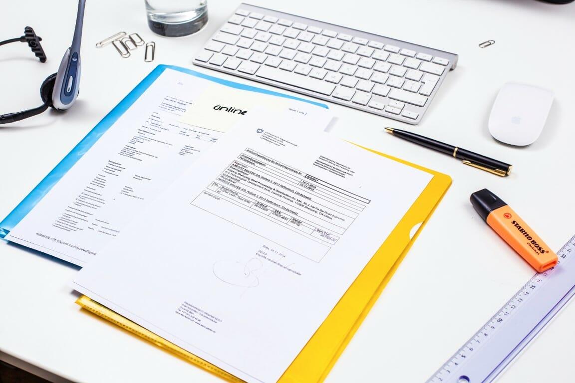 Dokumente im und auf Schnellhefter, sowie Stifte, Lineal, Tastatur und Maus